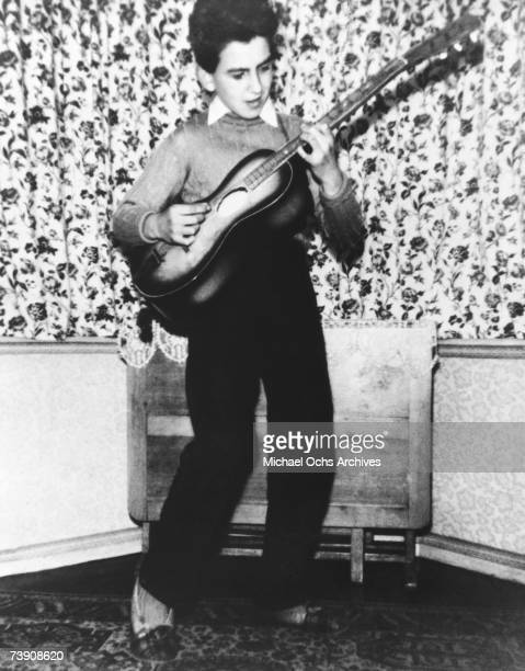 Guitarist George Harrison of the rock and roll band 'The Beatles' poses for a childhood portrait playing an acoustic guitar in circa 1954 in...