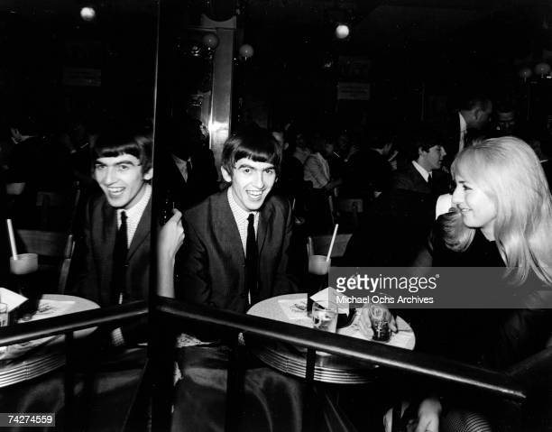 Guitarist George Harrison of the rock and roll band 'The Beatles' sits at a table with Cynthia Lennon at The Peppermint Lounge on their first night...