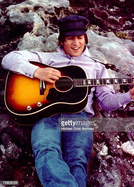 Guitarist John Lennon of the rock and roll band 'The Beatles' poses for a portrait while strumming a Gibson acoustic guitar and leaning against some...