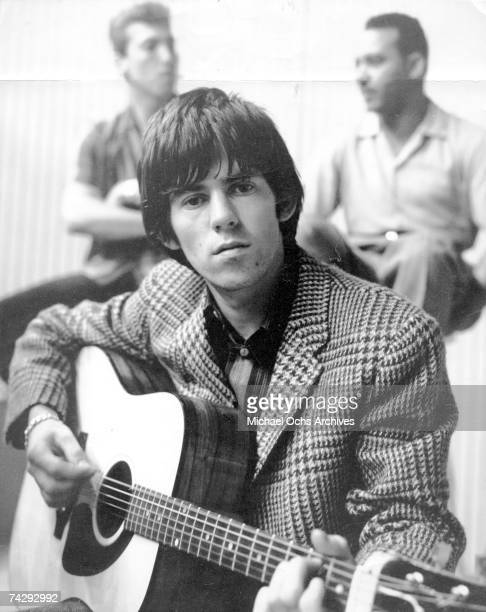 Guitarist Keith Richards of the rock band 'the Rolling Stones' poses for a portrait with an acoustic guitar and two men in the background in 1964