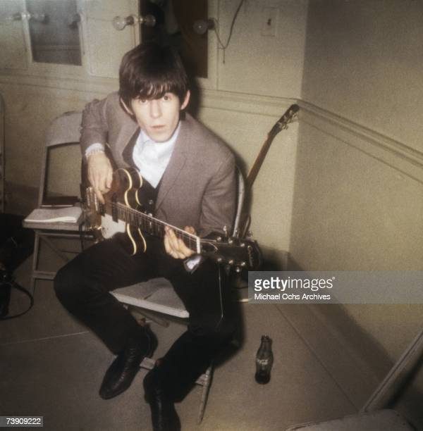 Guitarist Keith Richards of the rock band 'the Rolling Stones' sits on a chair and plays an Epiphone hollow body electric guitar with a Coca Cola...
