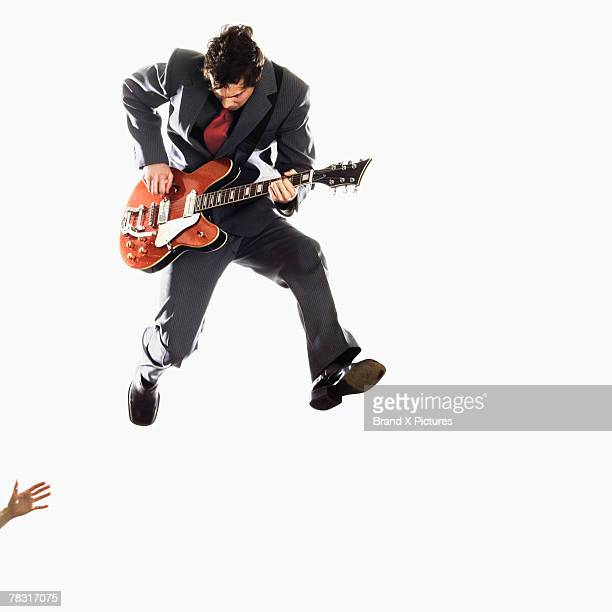 Guitarist leaping into air with guitar