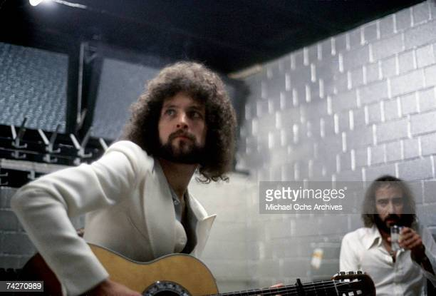 Guitarist Lindsey Buckingham and bassist John McVie of the rock group 'Fleetwood Mac' warm up backstage in July 1977