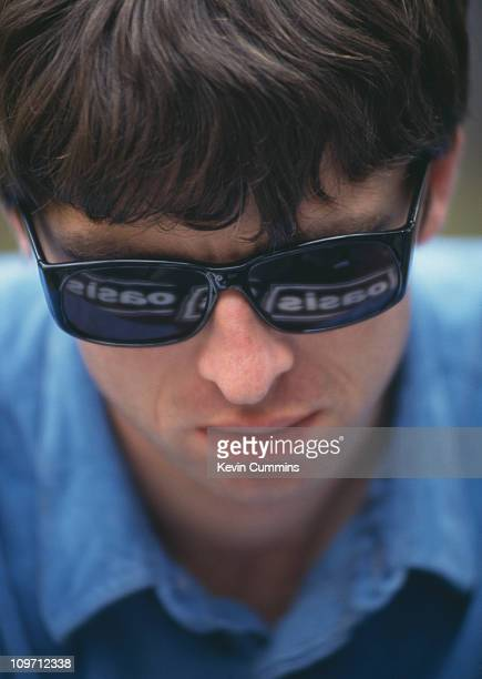 Guitarist Noel Gallagher of British pop group Oasis with the name of his group reflected in his sunglasses 2nd August 1994