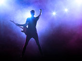 Silhouette of guitar player on stage on blue background with smoke and spotlights