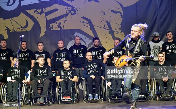 A guitarist performs as competitor attend the awards ceremony after the 'Games of the Heroes' crossfit challenge in Kiev on December 24 2016 Some...