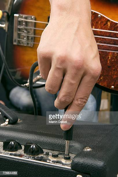 Guitarist plugging in amplifier