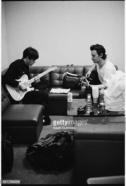Guitarist Richey James Edwards and singer James Dean Bradfield of Welsh alternative rock group the Manic Street Preachers playing guitars backstage...