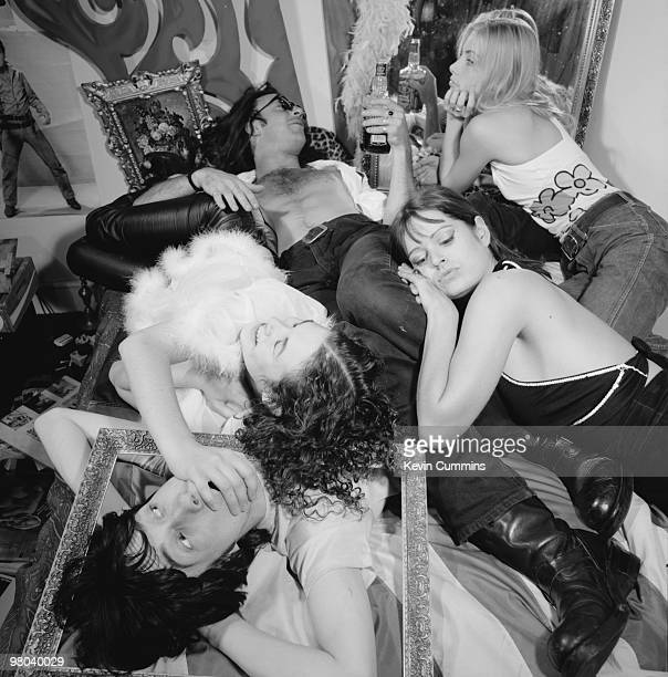 Guitarist Robert Young and singer Bobby Gillespie of Scottish rock group Primal Scream pose with women friends in a scene of archetypal rock 'n' roll...