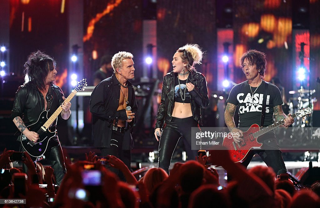 Guitarist Steve Stevens, singer Billy Idol, entertainer Miley Cyrus and guitarist Billy Morrison perform at the 2016 iHeartRadio Music Festival at T-Mobile Arena on September 23, 2016 in Las Vegas, Nevada.