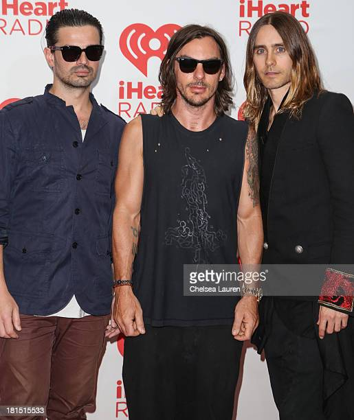 Guitarist Tomo Milicevic drummer Shannon Leto and vocalist Jared Leto of 30 Seconds to Mars pose in the iHeartRadio music festival photo room on...