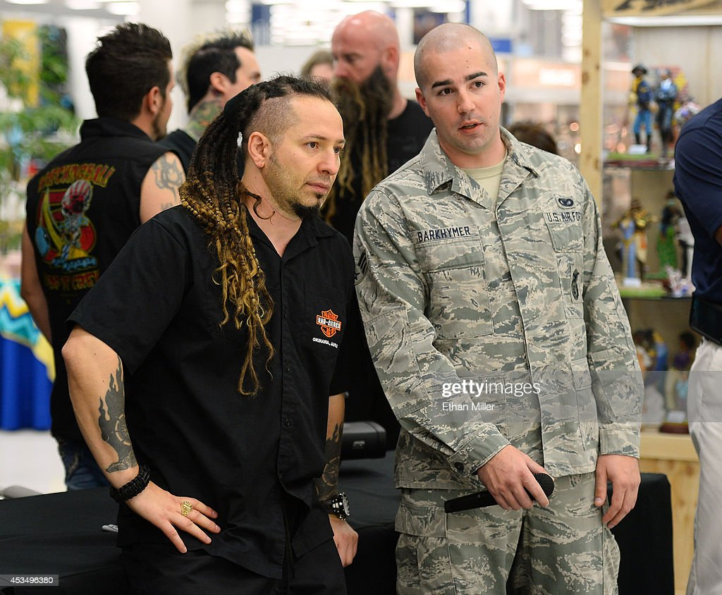 Guitarist Zoltan Bathory (L) of Five Finger Death Punch talks with Senior Airman Zachary Barkhymer at Nellis Air Force Base as the band highlights its campaign to raise awareness about veterans suffering from post-traumatic stress disorder (PTSD), in part by launching the video 'Wrong Side of Heaven,' that deals with the subject on August 11, 2014 in Las Vegas, Nevada.