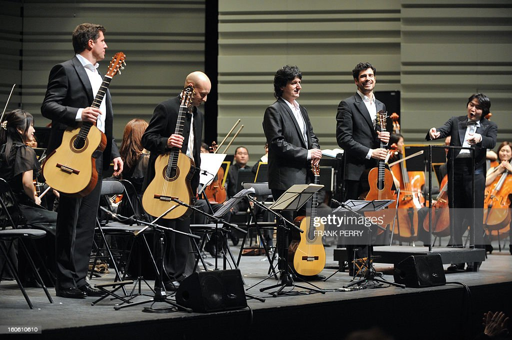 Guitarists Emmanuel Rossfelder, Fernando Espi, Juan Manuel Canizares, and Pablo Sainz Villegas salute after performing with the Yokohama Sinfonietta conducted by Kazuki Yamada (R), on February 3, 2013, as part of the 'Folle Journee' music festival at the Cite des Congres in Nantes.