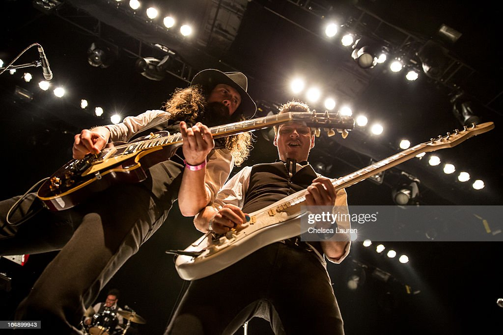 Guitarists Johnny Schreffler (L) and Dave Goodison perform the Vans Warped Tour press conference and kick-off party at Club Nokia on March 28, 2013 in Los Angeles, California.