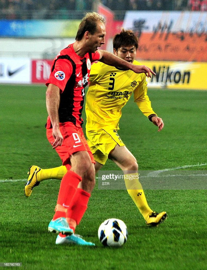 Guizhou Renhe's Zlatan Muslimovic (L) tussles for the ball with Kashiwa Reysol's Kondo in the AFC Champions group H match in Guiyang Olympic Centre Stadium, southwest China's Guizhou province on February 27, 2013. Kashiwa beat Guizhou 1-0. AFP PHOTO