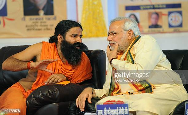 Gujarat state chief minister Narendra Modi and yoga guru Baba Ramdev chat during the 'Tarun Kranti Puraskar' award function in Ahmedabad on July 29...