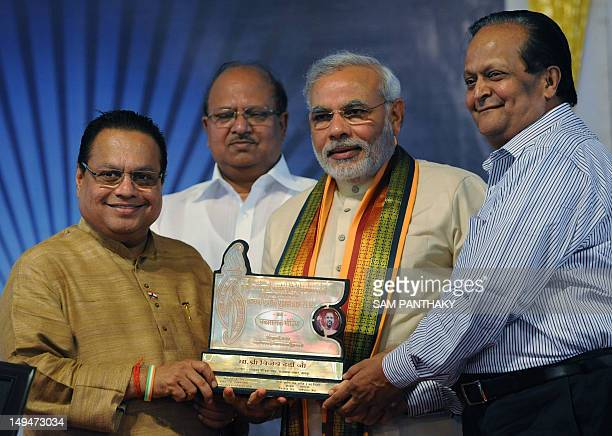 Gujarat state chief minister Narendra Modi presents the'Tarun Kranti Puraskar' award to Congress Member of Parliament Vijay Darda as chairman of the...