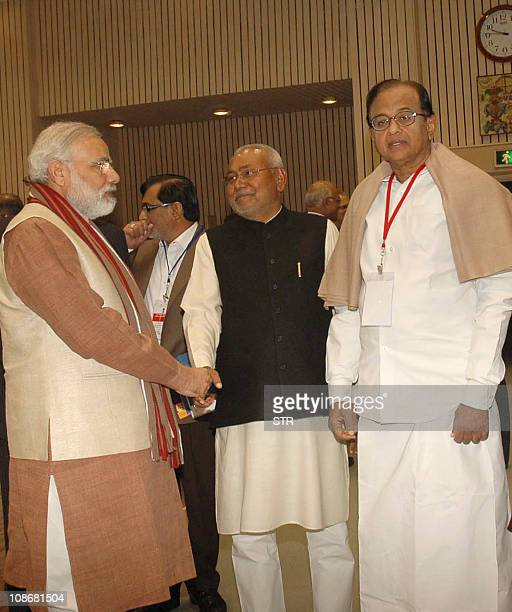 Gujarat state Chief Minister Narendra Modi shakes hands with Bihar chief minister Nitish Kumar as Indian Home Minister P Chidambaram looks on during...