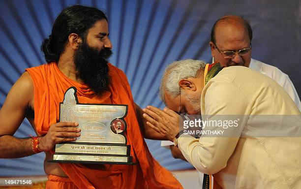 Gujarat state chief minister Narendra Modi takes blessings from yoga guru Baba Ramdev after presenting him with the 'Tarun Kranti Puraskar' during an...