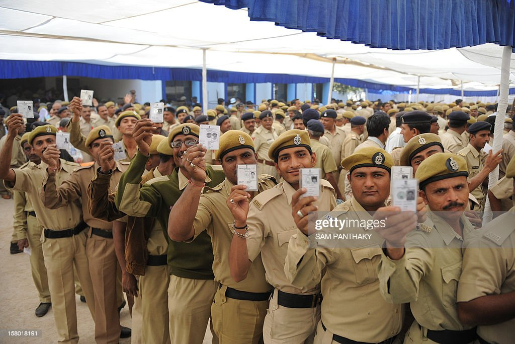 Gujarat state police and Home Guard officials pose with their voter identity cards at The Postal Ballot Issue Centres at the Police Head Quarters (HQ) in Ahmedabad on December 9, 2012. Large numbers of police officials and homeguards thronged to cast their votes ahead of time by special arrangments made by the election commission for servicemen on duty in the forthcoming Gujarat state elections scheduled for December 13 and 17. AFP PHOTO / Sam PANTHAKY
