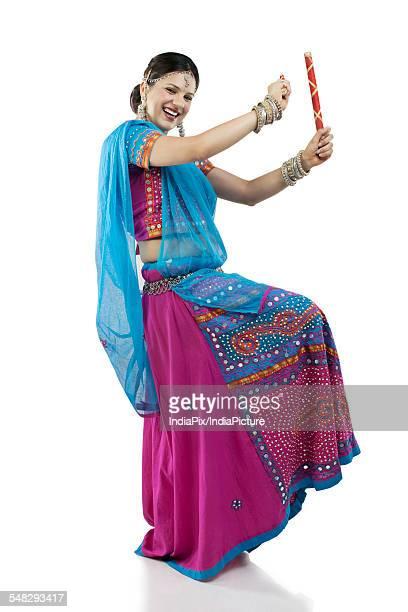 Gujarati woman dancing with dandiya sticks