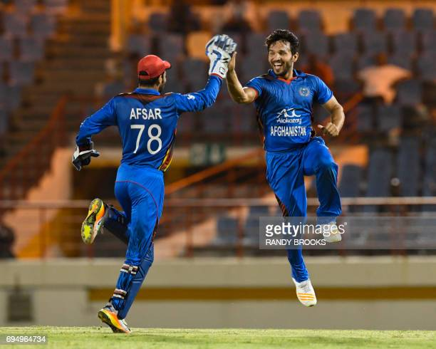 Gulbadin Naib and Afsar Khan Zazai of Afghanistan celebrate the dismissal of Jason Mohammed of West Indies during the 2nd ODI match between West...