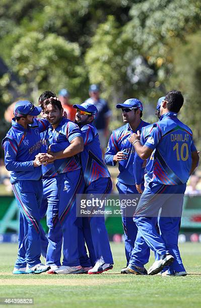 Gulbadin Naib of Afghanistan celebrates taking the wicket of Preston Mommsen of Scotland with his teammates during the 2015 ICC Cricket World Cup...