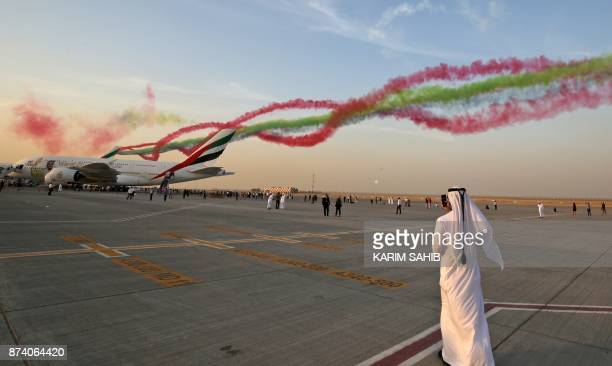A Gulf Arab watches the United Arab Emirates' AlFursan display team perform during the Dubai Airshow on November 14 in the Gulf emirate / AFP PHOTO /...