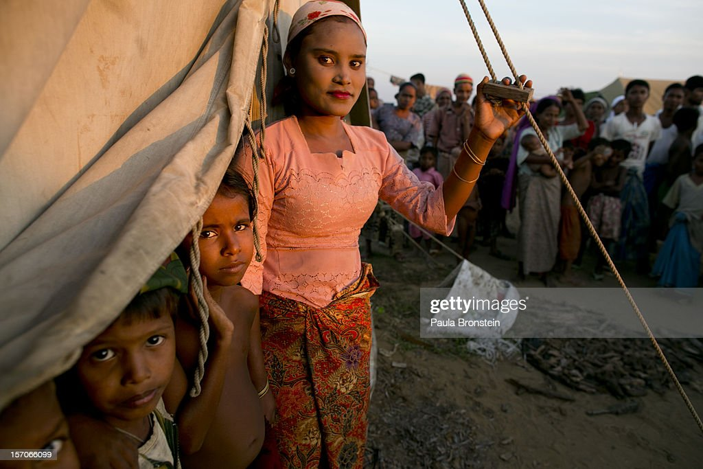 Gulzar looks out from her tent along side her children at a crowded IDP camp November 25, 2012 on the outskirts of Sittwe, Myanmar. An estimated 111,000 people were displaced by sectarian violence in June and October effecting mostly the ethnic Rohingya people who are now living in crowded IDP camps racially segregated from the Rakhine Buddhists in order to maintain stability. Around 89 lives were lost during a week of violence in October, the worst in decades. As of 2012, 800,000 Rohingya live in Myanmar. According to the UN, they are one of the most persecuted minorities in the world.