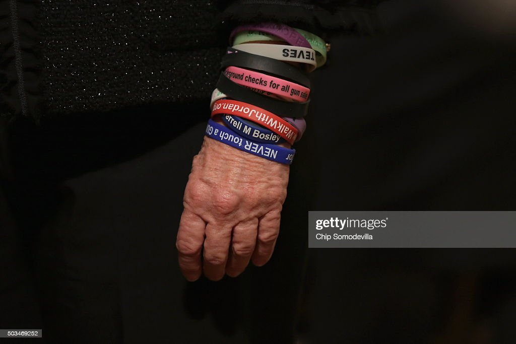 A gun control advocate wears a series of plastic advocacy bracelets while waiting for U.S. President Barack Obama to deliver remarks about his efforts to increase federal gun control in the East Room of the White House January 5, 2016 in Washington, DC. Without approval from Congress, Obama is sidestepping the legislative process with executive actions to expand background checks for some firearm purchases and step up federal enforcement of existing gun laws.