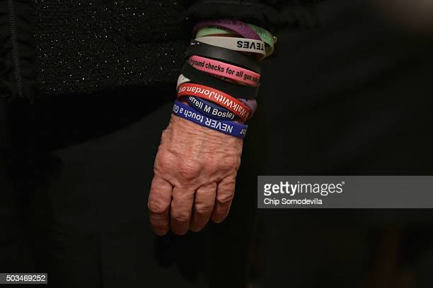 A gun control advocate wears a series of plastic advocacy bracelets while waiting for US President Barack Obama to deliver remarks about his efforts...