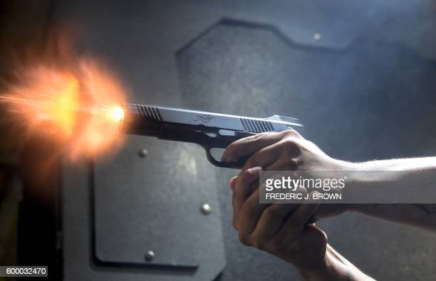 A gun enthusiast fires his Kimber 1911 pistol at the LAX Firing Range in Inglewood California on September 7 2016 / AFP PHOTO / Frederic J BROWN