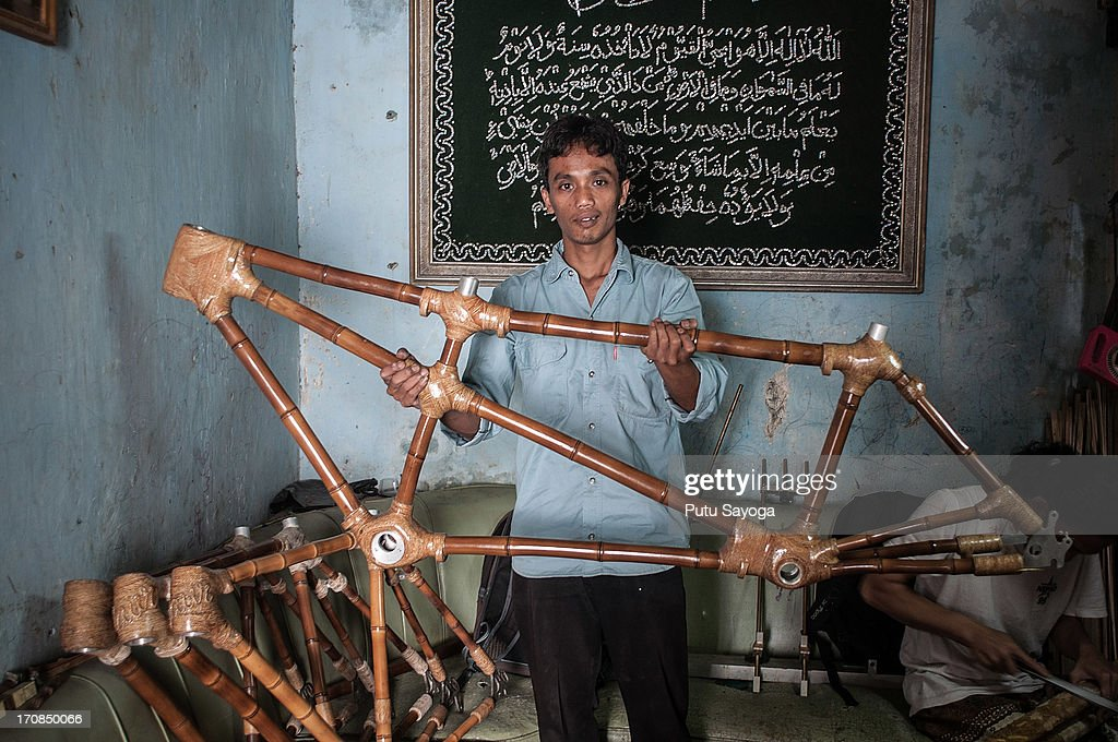 Gun Gun Gunawan poses with a tandem bamboo bike frame at Haur Bike workshop on June 19, 2013 in Bandung, Java, Indonesia. Two friends, Abah and Gun Gun Gunawan converted Abah's small guest room into a workshop in the Neglasari district in order to make bamboo bikes with sustainable phyllostachys aurea bamboo using DIY tools. They have named their product 'Haur Bike'.