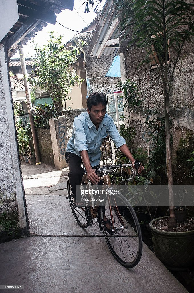 Gun Gun Gunawan tests a bamboo bike in an alley near Haur Bike workshop on June 19, 2013 in Bandung, Java, Indonesia. Two friends, Abah and Gun Gun Gunawan converted Abah's small guest room into a workshop in the Neglasari district in order to make bamboo bikes with sustainable phyllostachys aurea bamboo using DIY tools. They have named their product 'Haur Bike'.
