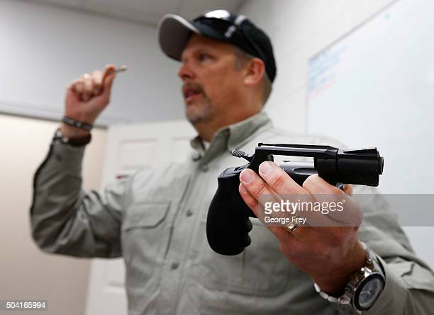 Gun instructor Mike Stilwell demonstrates a revolver as as he teaches a packed class to obtain the Utah concealed gun carry permit at Range Master of...