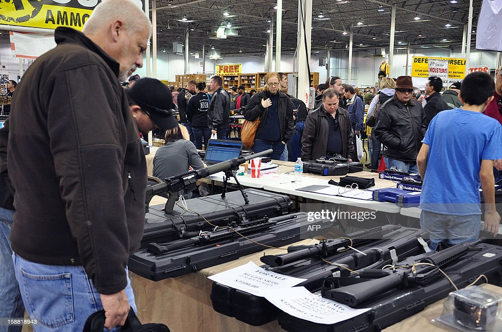 Gun show goers look at various assault-style weapons December 30, 2012 at the Nation's Gun Show in Chantilly, Virginia. Since the Connecticut school shootings, gun sales, particularly assault-style weapons have gone up sharply. AFP PHOTO/Guillaume MEYER