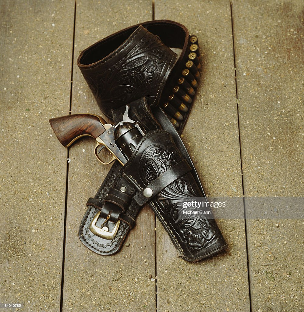 Gun with holster and bullets on wooden floor : Stock Photo