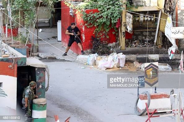 A gunman belonging to Palestinian president Mahmud Abbas's Fatah movement take position near an Lebanese army checkpoint at the entrance of the Ain...