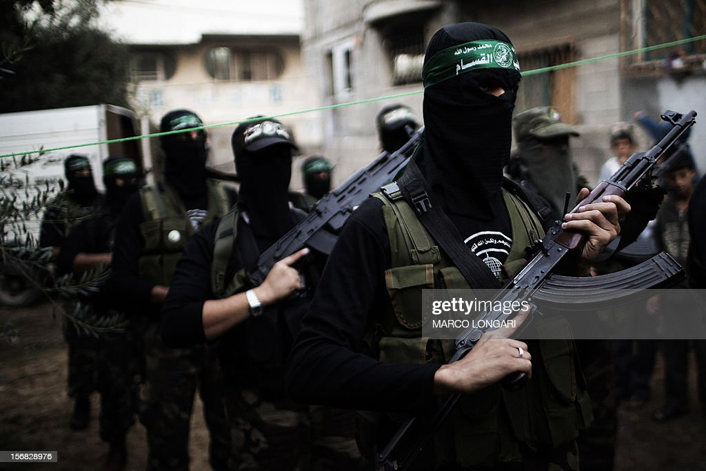 Gunmen from the Ezzedine al-Qassam Brigades, the armed wing of Hamas, line up outside the house of their late leader Ahmed Jaabari, as mourners visit his family to pay their condolences in Gaza City on November 22, 2012. Israeli politicians returned to the campaign trail as the streets of Gaza came back to life after a truce ended eight days of bloodshed, with both sides claiming victory while remaining wary. AFP PHOTO/MARCO LONGARI