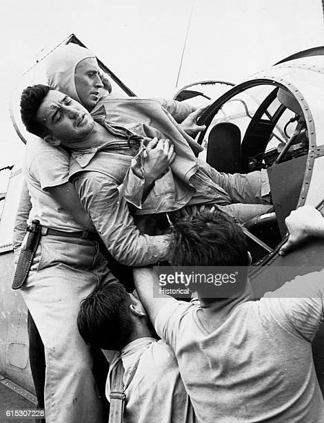 Gunner Kenneth Bratton is taken out of the turret of a torpedobomber on the USS Saratoga after being wounded during a raid against Rabaul Bratton had...