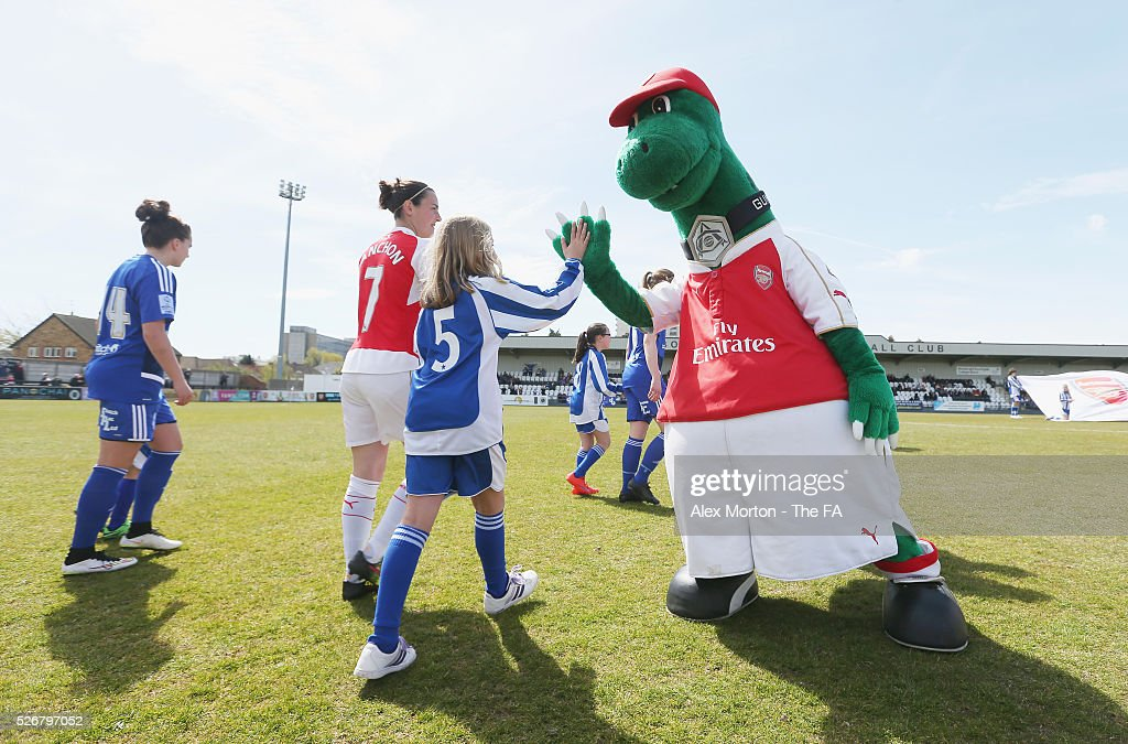 Gunnersaurus high fives a mascot prior to the WSL match between Arsenal Ladies and Birmingham City Ladies at Meadow Park on May 1, 2016 in Borehamwood, England.