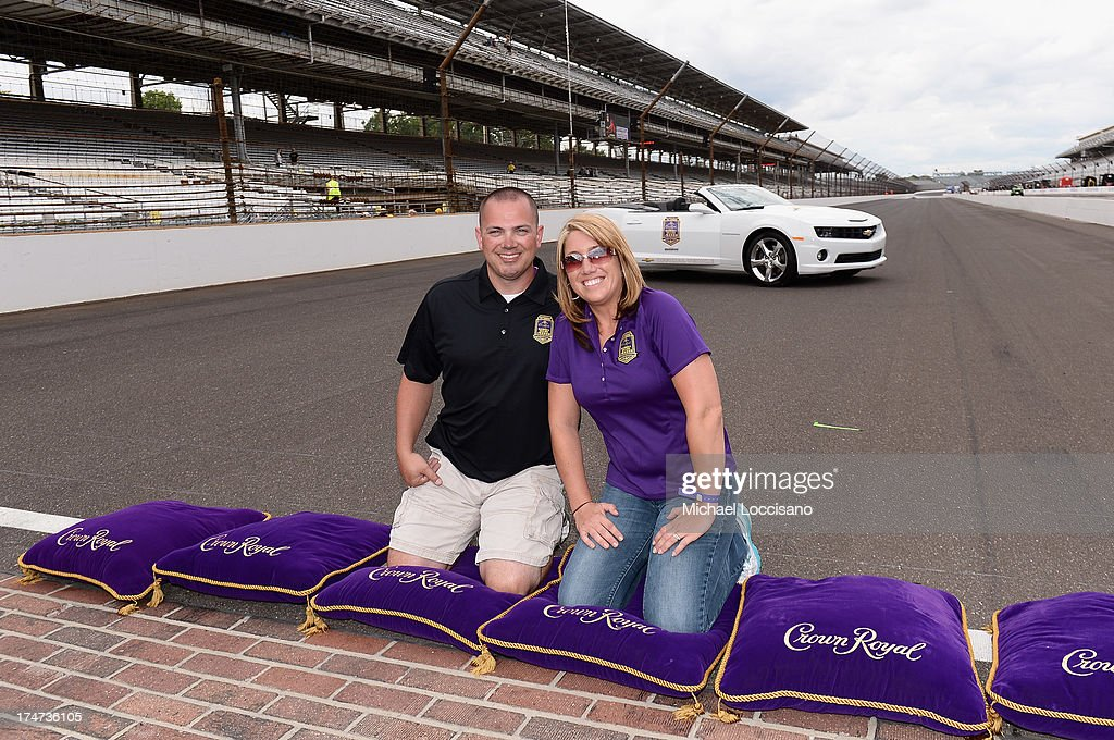 Gunnery Sergeant Samuel Deeds and his wife April kiss the bricks at Indianapolis Motor Speedway on July 28, 2013 in Indianapolis, Indiana. As winner of the annual Crown Royal 'Your Hero's Name Here' program, Deeds received naming rights to the July 28th NASCAR Sprint Cup Series race at the Brickyard.
