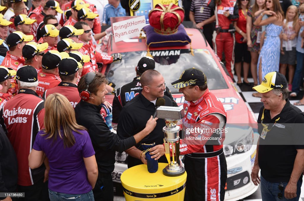 Gunnery Sergeant Samuel Deeds and his wife April pose with winner Ryan Newman at Indianapolis Motor Speedway on July 28, 2013 in Indianapolis, Indiana. As winner of the annual Crown Royal 'Your Hero's Name Here' program, Deeds received naming rights to the July 28th NASCAR Sprint Cup Series race at the Brickyard.