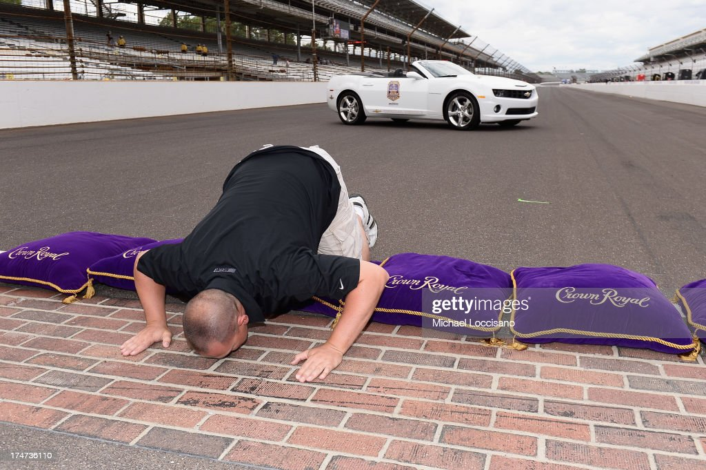 Gunnery Sergeant Samuel Deeds kisses the bricks at Indianapolis Motor Speedway on July 28, 2013 in Indianapolis, Indiana. As winner of the annual Crown Royal 'Your Hero's Name Here' program, Deeds received naming rights to the July 28th NASCAR Sprint Cup Series race at the Brickyard.
