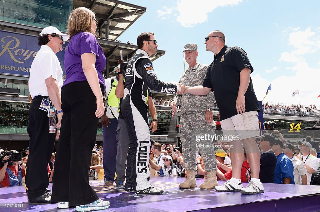 Gunnery Sergeant Samuel Deeds shakes hands with NASCAR driver Jimmie Johnson at Indianapolis Motor Speedway on July 28, 2013 in Indianapolis, Indiana. As winner of the annual Crown Royal 'Your Hero's Name Here' program, Deeds received naming rights to the July 28th NASCAR Sprint Cup Series race at the Brickyard.