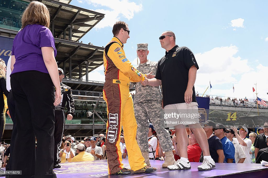 Gunnery Sergeant Samuel Deeds shakes hands with NASCAR driver <a gi-track='captionPersonalityLinkClicked' href=/galleries/search?phrase=Kyle+Busch&family=editorial&specificpeople=211123 ng-click='$event.stopPropagation()'>Kyle Busch</a> at Indianapolis Motor Speedway on July 28, 2013 in Indianapolis, Indiana. As winner of the annual Crown Royal 'Your Hero's Name Here' program, Deeds received naming rights to the July 28th NASCAR Sprint Cup Series race at the Brickyard.