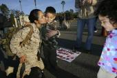 Gunnery Sgt Deborah Dangremond kisses her son Tyler as her daughter Basia looks on Marines and sailors of the 1st Marine Logistics Group return home...