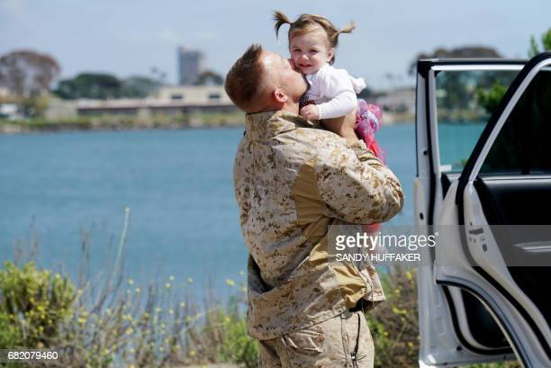Gunnery Sgt Michel Grabau hugs his daughter Mikaelie during a homecoming reception at Camp Pendleton in Oceanside California on May 11 2017 arines...