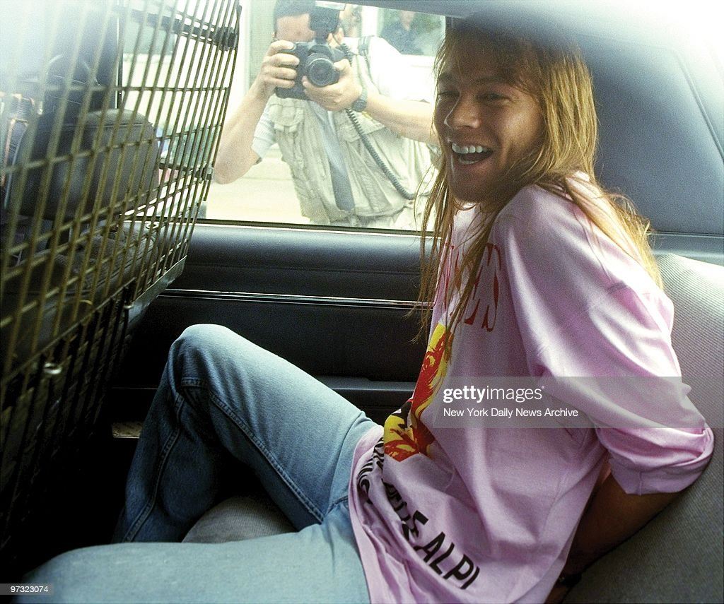 Guns N' Roses lead singer Axl Rose sits handcuffed in the back of a police car after he was arrested at Kennedy Airport upon his return from a European concert tour. Rose was charged with four counts of misdemeanor assault and one count of property damage stemming from a riot during a concert in 1991 in St. Louis. Rose pleaded innocent to the charges, and was later given two years probation and forced to donate $50,000 to charity.