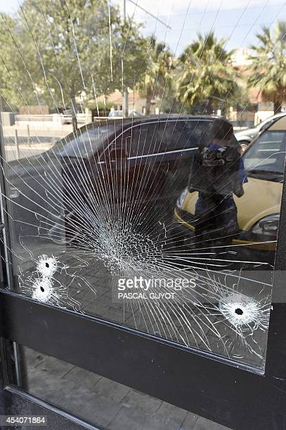 Gunshot holes are seen on August 24 2014 on the door at the entrance of an apartment building where two men was shot dead during the night of 23 to...